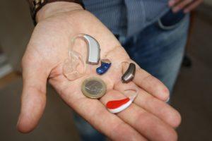 Kädellä kuulokojeita ja euron kolikko.