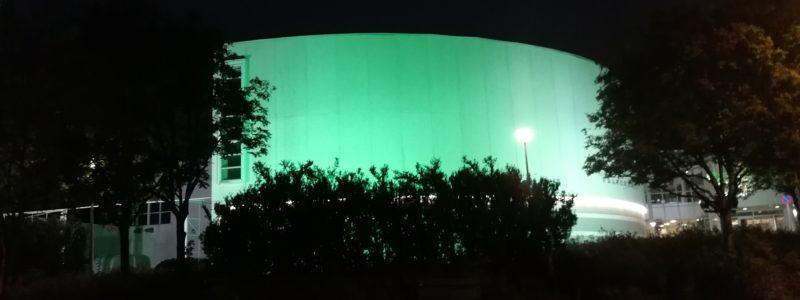 Valkea talo vihreässä valaistuksessa.