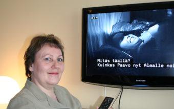 Nainen katsoo televisiotekstitettyä ohjelmaa.