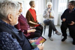 Joukko ihmisiä istuu ringissä älylaitteet sylissään. Puhuja puhuu mikrofoniin. Kuuntelijat seuraavat puhetta kuulokojeet korvissa.