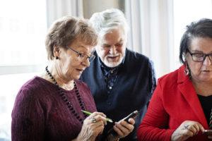 Kolme ihmistä katsovat älypuhelimiaan.