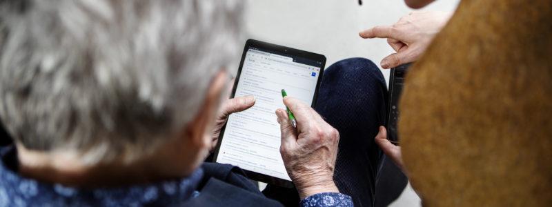 Kaksi henkilöä ovat tabletin äärellä. Vasemmalla herrasmies katsoo tablettia digikynä kädessään. Oikealla seisova henkilö neuvoo.