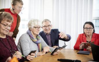 Neljä ihmistä pöydän äärellä tekevät jotain älypuhelimillaan. Yksi heistä neuvoo vieressä istuvaa henkilöä. Viides henkilö seuraa seisoen, mitä tilanteessa tapahtuu.
