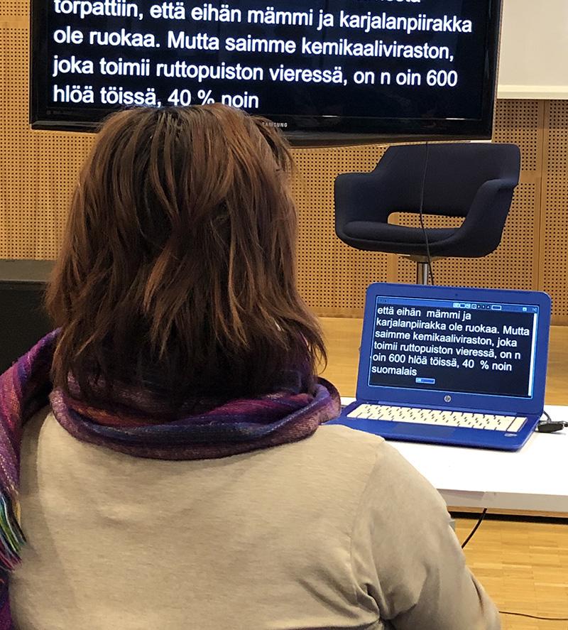 Kirjoitustulkki työssään. Edessä näkyy kannettava tietokone ja televisio.