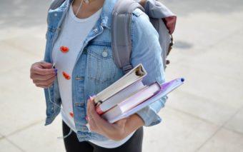 Nainen kävelee. Hänellä on reppu selässä ja pino kirjoja kädessä.