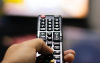 Television kaukosäädin kädessä.
