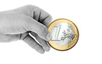 Käsi, jossa on yhden euron kolikko