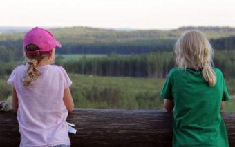 Lapset katsovat metsämaisemaa.