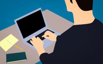 Mieshahmo työskentelee kannettavalla tietokoneella.