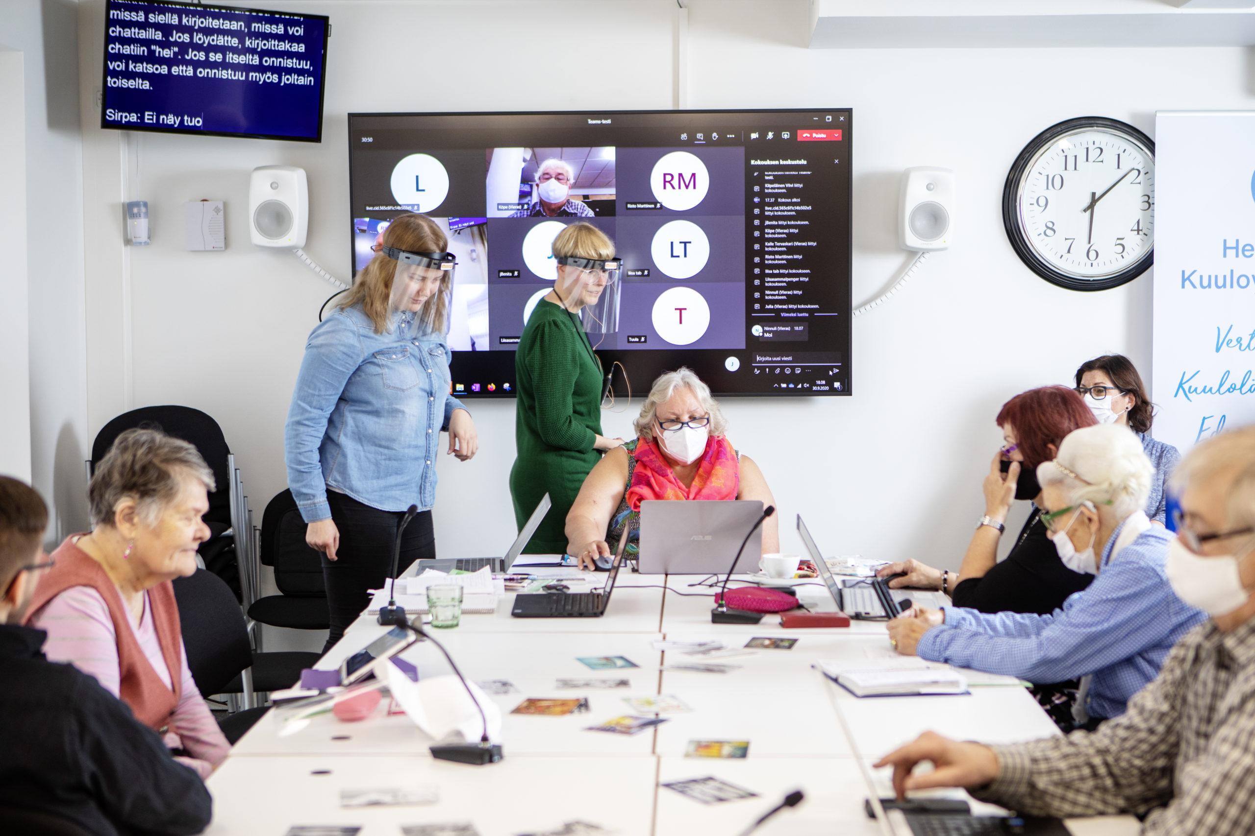Joukko osallistujia on pöydän ympärillä tietokoneiden äärellä. Osallistujilla on kasvomaskit. Taustalla pyörii Zoom-etätapaaminen.