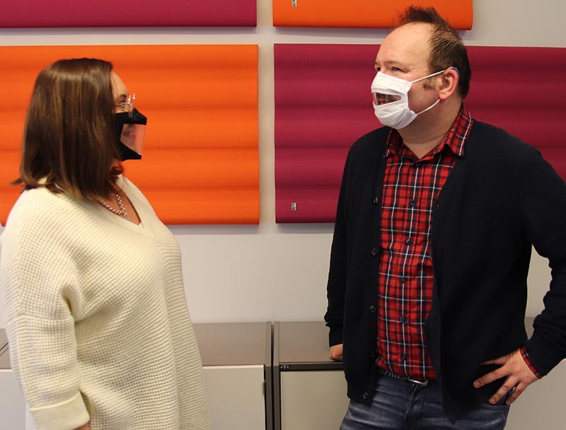 Nainen ja mies keskustelevat ja heillä on kasvoillaan ikkunalliset maskit.