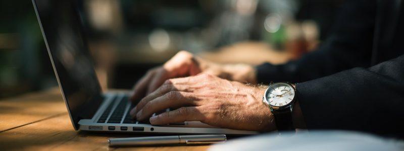 Mies kirjoittaa tietokoneella