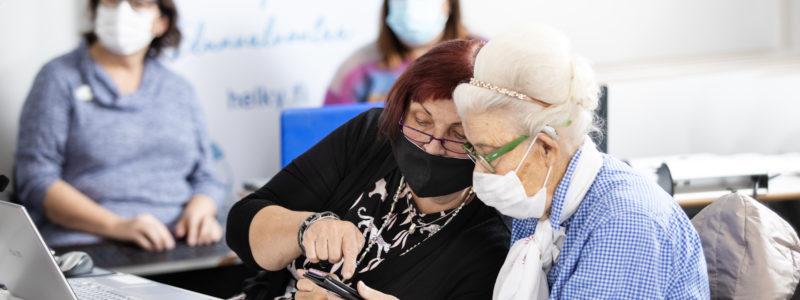 Kaksi henkilöä katsovat maskit kasvoilla toisen älypuhelinta