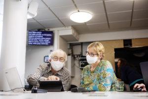 Kaksi henkilöä katsovat maskit kasvoilla tablettia.