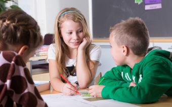 Tyttö ja poika tekevät yhdessä koulutehtävää.