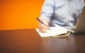 Henkilö kirjoittaa vihkoon. Pöydällä on kannettava tietokone.