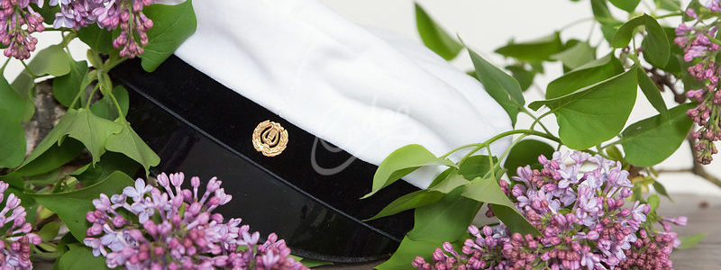 Ylioppilaslakki syreenin kukkien keskellä valkoista taustaa vasten.