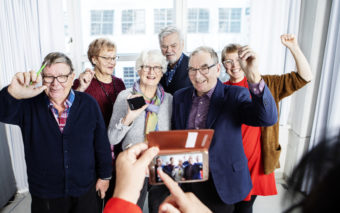 Kuusi iloista, eri-ikäistä ihmistä ovat kuvattavina.