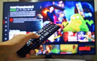 Henkilöllä on kaukosäädin kädessään. Taustalla näkyy tv-ruutu.