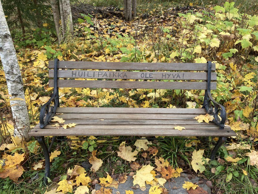 Puistonpenkkiin on kirjoitettu huilipaikka ole hyvä. Maassa on keltaisia vaahteranlehtiä.